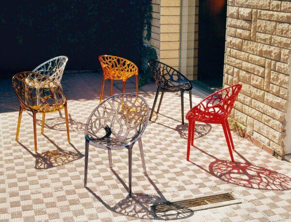 Exteriérová stolička SI-CRYSTAL vo viacerých kusoch červenej, hnedej a jantárovej farby na terase