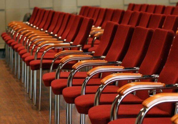 Rokovacie stoličky NS-loco v červenej farbe umiestnené vedľa seba v konferenčnej mmiestnosti.