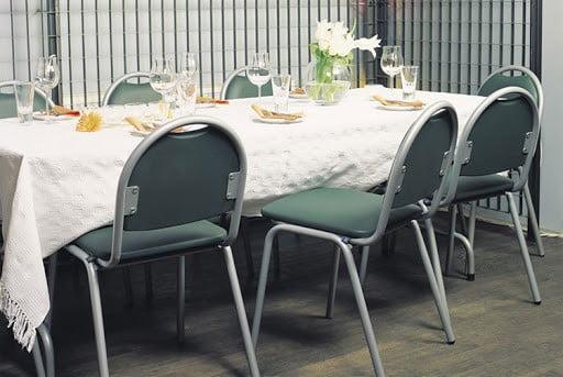 Stolička NS-Arioso v zelenej farbe otočená zozadu, zasunutá pod stolom v reštaurácií.
