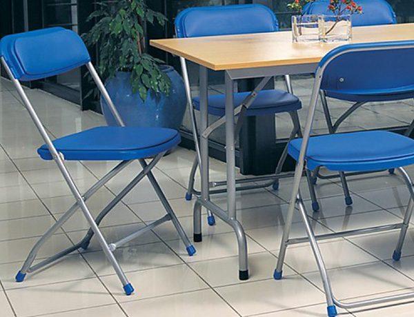 Stolička NS-Polyfold v tmavomodrej farbe umiestnená v priestore jedálne pri stole.