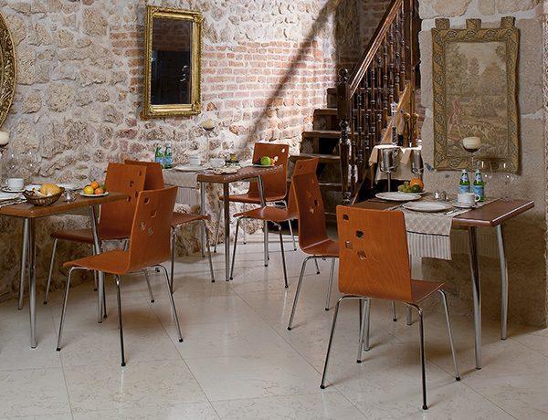 Stolička NS-Ammi v hnedej farbe dreva je umiestnená vo viacerých kusoch v reštaurácií.