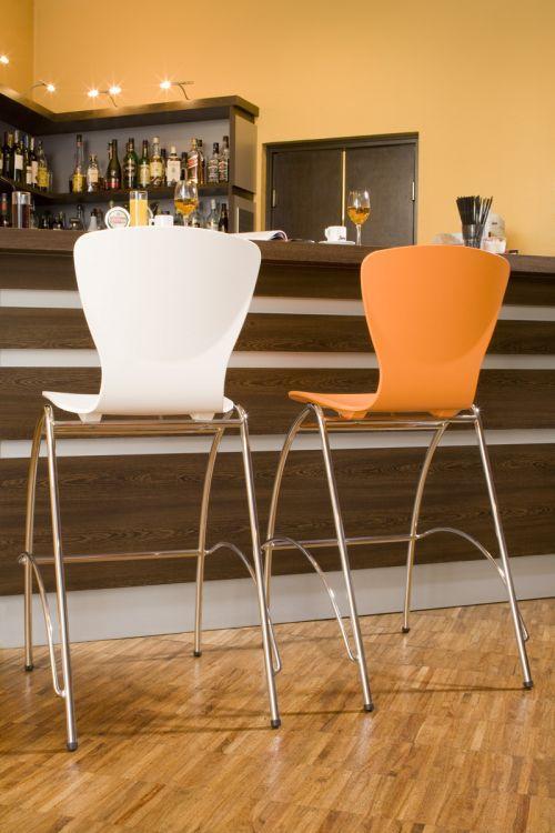Barová stolička NS-Bingo v dvoch kusoch, v bielej a oranžovej farbe stojace pri bare.