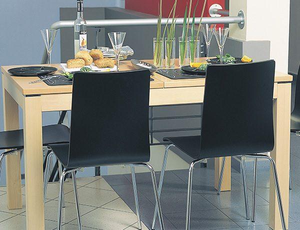 Stoličky NS-Cafe otočené zozadu v čiernom prevedení umiestnené v kuchyni za stolom.