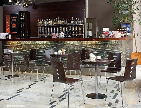 Stolička NS-Lantana vo viacerých kusoch hnedej farby umiestnená v útulnej kaviarni.