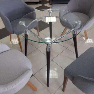 Sklenený stolík NS-Algeo ST s drevenými nohami a skleneným plátom medzi kreslami v interiéri.
