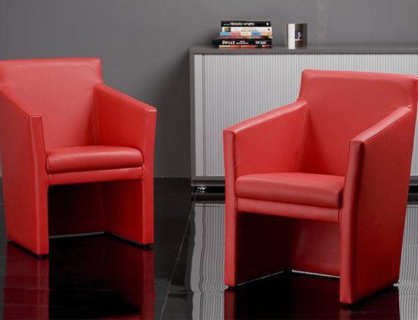 Kreslo NS-Club SQ v červenej farbe v dvoch kusoch, umiestnené v interiéri.