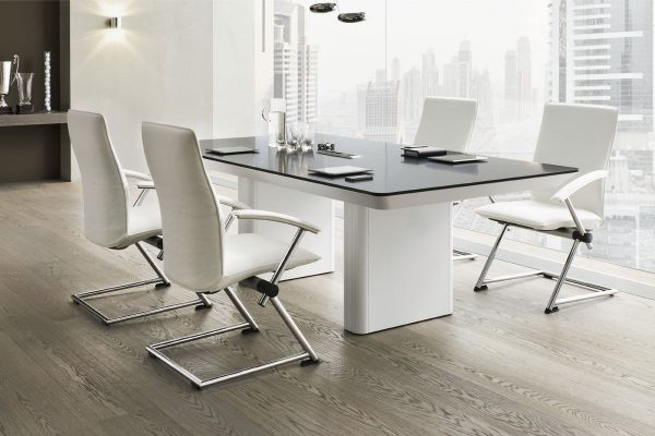 Rokovací stôl Ns-eRange v bielej farbe so stoličkami umiestnený v rokovacej miestnosti.